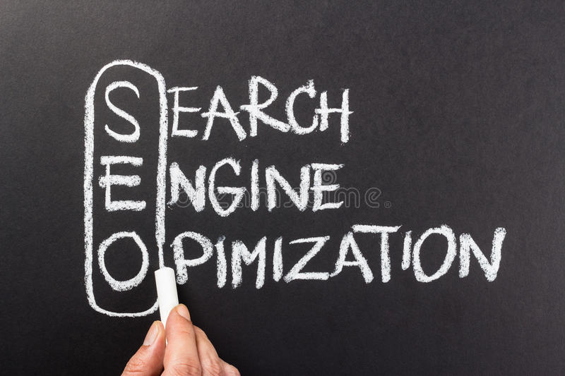 SEO. Hand writing Search Engine Optimization (SEO) topic with chalk royalty free stock images