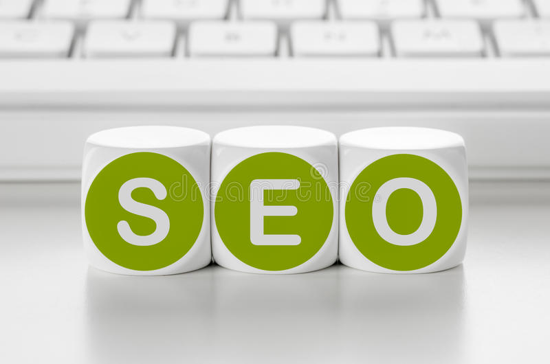 SEO. Letter dice in front of a keyboard - SEO royalty free stock photos