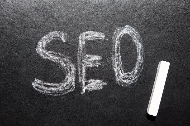 SEO - optimización del Search Engine, texto en la pizarra negra con la tiza blanca foto de archivo libre de regalías