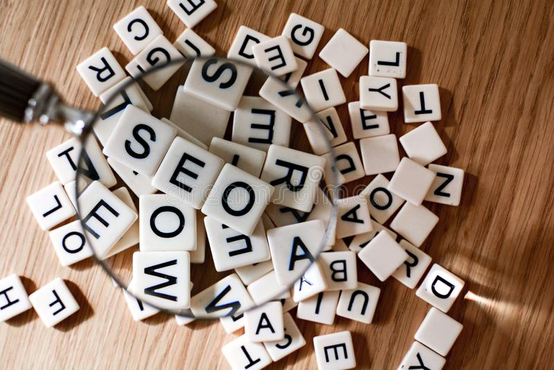 SEO pojęcie z powiększać - szkło nad SEO tekstem literującym za mieszanych listach od zdjęcia stock