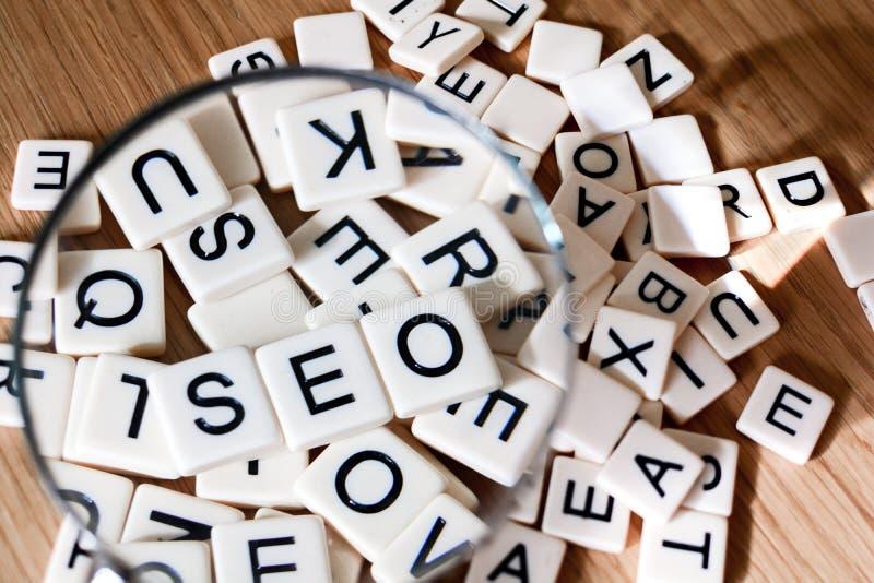 SEO pojęcie z powiększać - szkło nad SEO tekstem literującym za mieszanych listach od zdjęcie stock