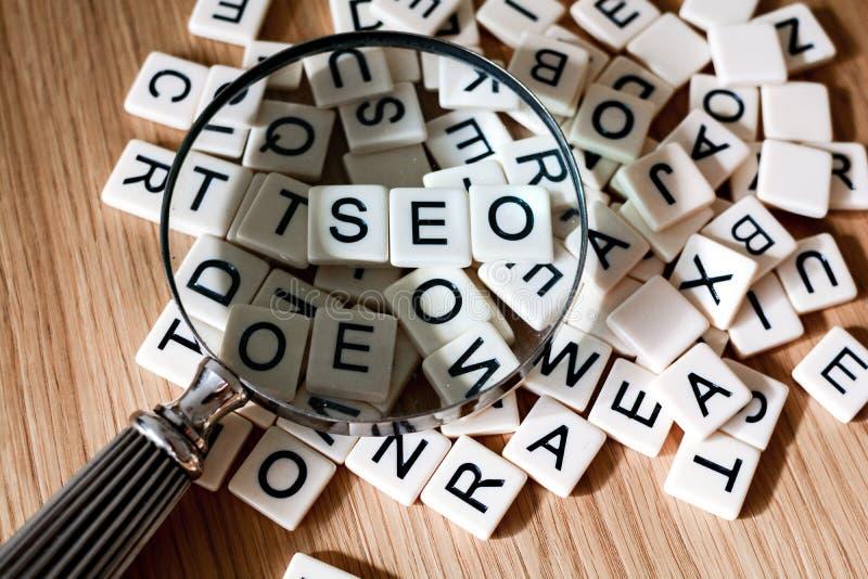 SEO pojęcie z powiększać - szkło nad SEO tekstem literującym za mieszanych listach od zdjęcie royalty free