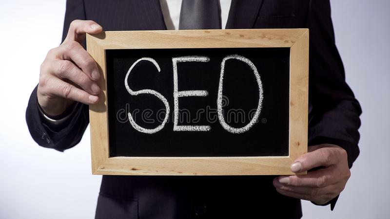 SEO scritto sulla lavagna, segno della tenuta dell'uomo d'affari, concetto di affari, strategia fotografie stock
