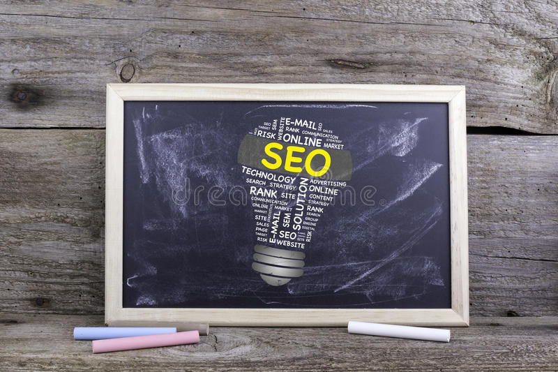SEO (search engine optimization) bulb word cloud. Chalk board on royalty free stock images