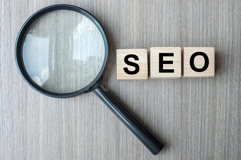 SEO Search Engine Optimization text wooden cubes and magnifying glass on wood table background. Idea, Vision, Strategy, Analysis. Keyword and Content royalty free stock photo