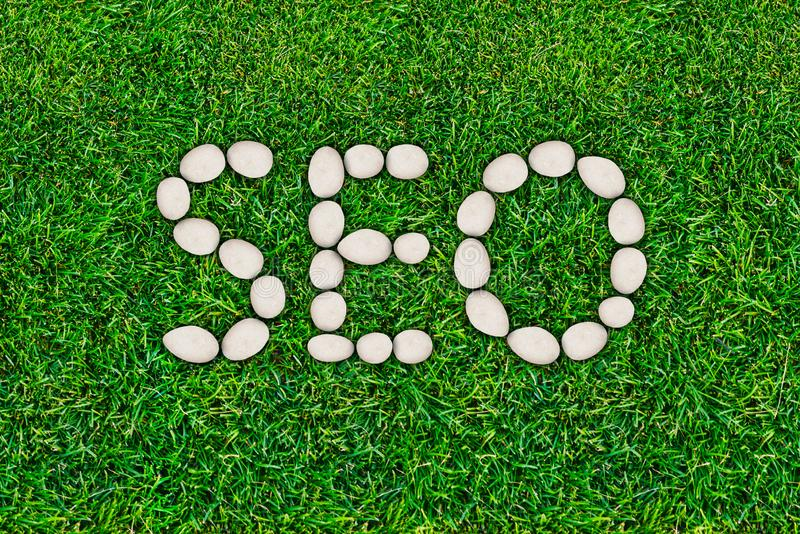 SEO, search engine optimization. Website traffic promotion. Internet technologies. The word laid out on the lawn royalty free stock image