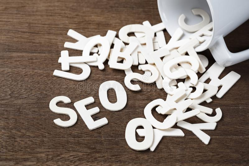 SEO Spill Out. Wood letters spill out of a cup as SEO word royalty free stock photo