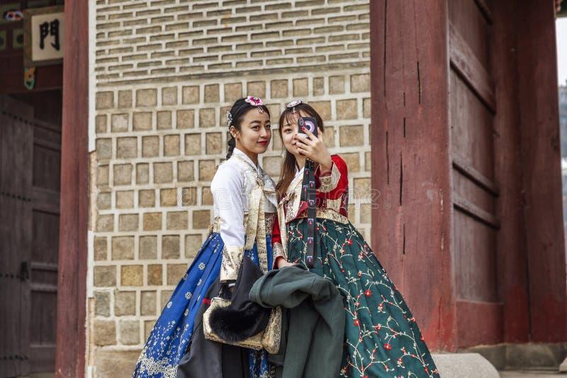 Seoel, Zuid-Korea, 12/30/2017: De Koreaanse meisjes in hanboks nemen een selfie in een de winterpark stock foto's