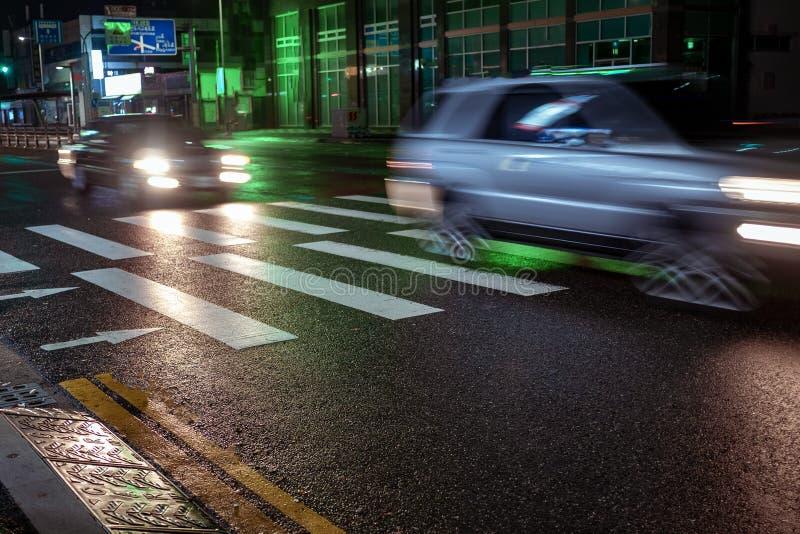 Seoel, Zuid-Korea - 30 10 18: twee auto'spas snel bij nacht op een voetgangersoversteekplaats royalty-vrije stock foto