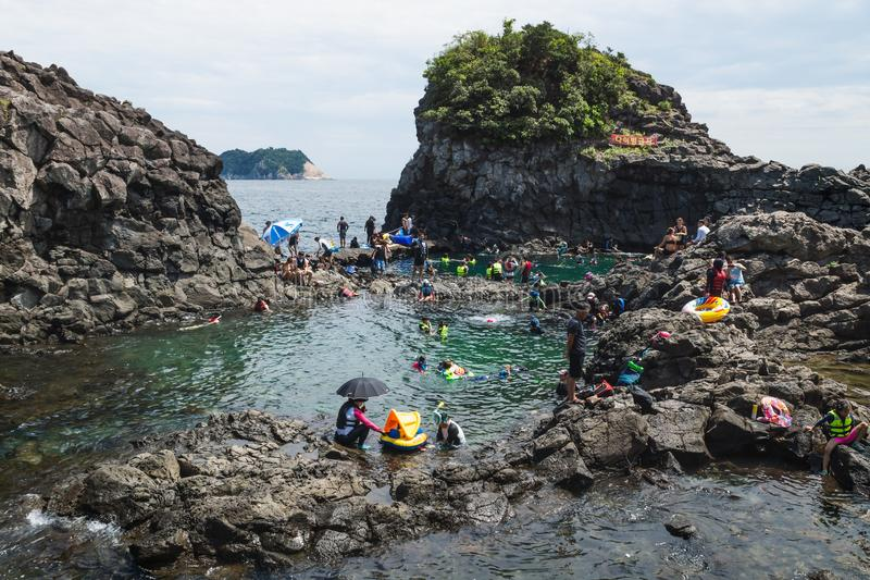 Natural Pool with a crowd of tourists and locals swimming at Seogwipo, Jeju Island, South Korea royalty free stock photography