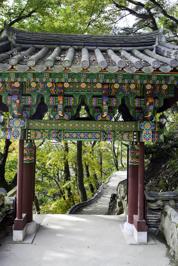 Seongjeongnam Hermitage Gate against autum leaves and stone path. Songjeonnam Hermitage is located in the Palgonsan Mountains north of Daegu. The beautiful gate stock image