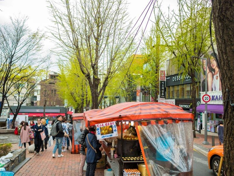 Seoul, Corea del Sud - 14 aprile 2018: Alimento d'acquisto della gente ad una stalla dell'alimento della via in via di Hongdae il immagini stock libere da diritti