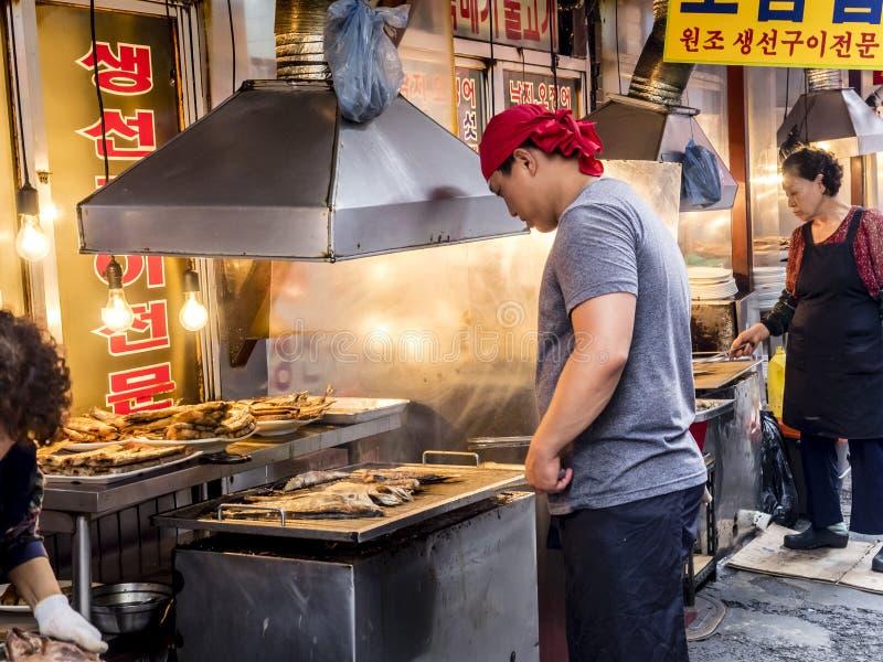 Seoul, Coreia do Sul - 21 de junho de 2017: Vendedor do homem que cozinha peixes fritados saborosos no mercado de Gwangjang em Se fotos de stock royalty free
