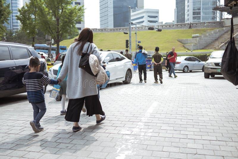 Seoul, Südkorea - 08 05 18: Mutter mit einem Kind, das entlang eine verkehrsreiche Straße geht lizenzfreies stockfoto