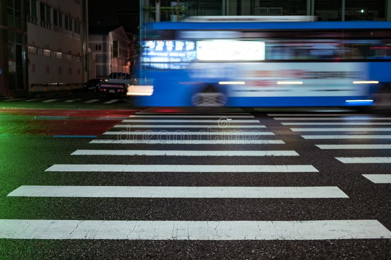 Seoul, South Korea - 30.10.18: a blue bus rushes past a pedestrian crossing at night. City bus quickly rides on wet asphalt stock image