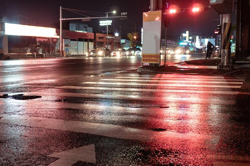 Seoul, South Korea - 30.10.18: Crosswalk with pointing arrow in the night in neon light. Wet asphalt in red light. the traffic flow is in front of the red stock image
