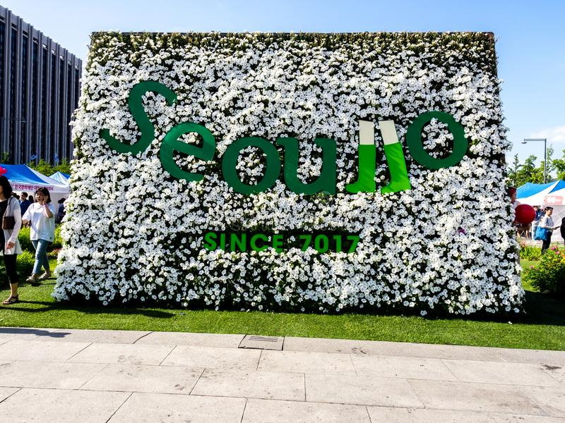 Seoul, South Korea - June 3, 2017: People walking in the Gwanghwamun Square near big flower bed with inscription: royalty free stock images