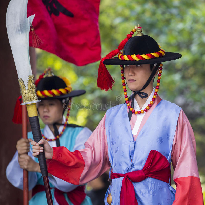 SEOUL, SOUTH KOREA - OCTOBER 20, 2016: Palace guards in traditional costumes solemnly guard the imposing main gate stock photography
