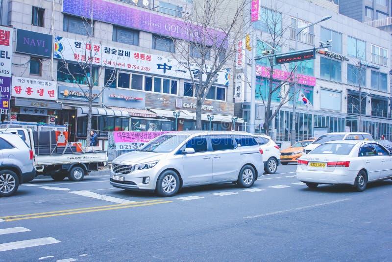 SEOUL SYDKOREA - December 29, 2014: Den upptaget gatan med bilar och olikt shoppar royaltyfria bilder