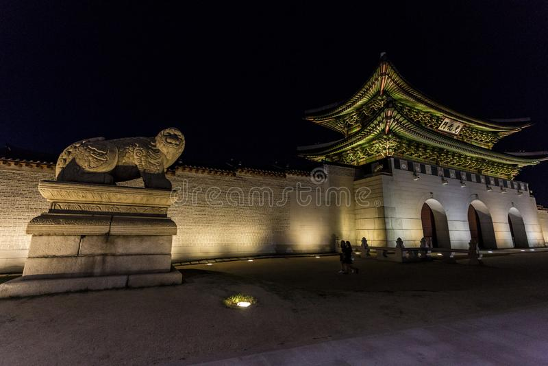 Seoul Sydkorea - Juni 1, 2017: Folk som går nära den Gwanghwamun porten på den Gyeongbokgung slotten på natten royaltyfri foto