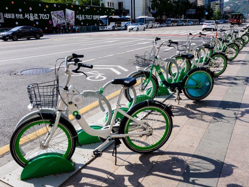 Seoul Sydkorea - Juni 3, 2017: Ljust - gröna cyklar som parkeras på trottoaren i centrum i Seoul arkivbilder