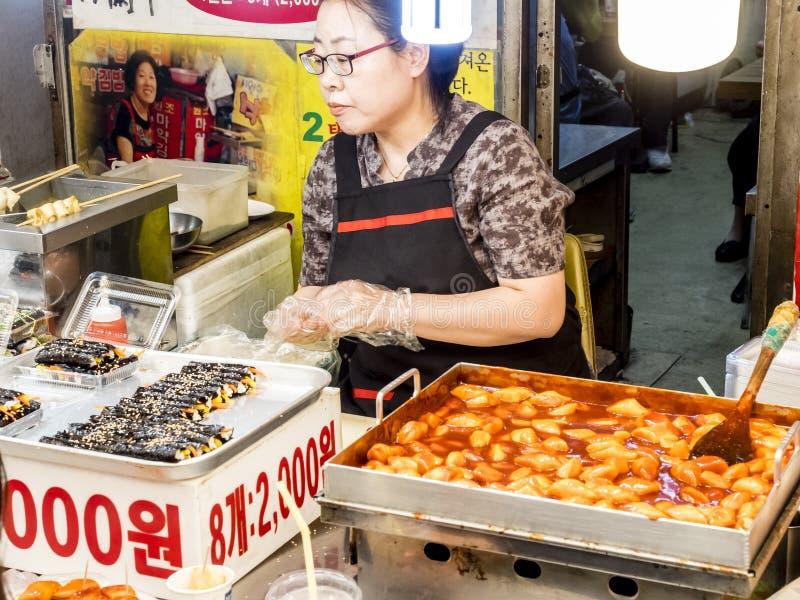 Seoul Sydkorea - Juni 21, 2017: Tjänande som kunder för kvinnaförsäljare på den Gwangjang marknaden i Seoul En av den populäraste royaltyfria foton