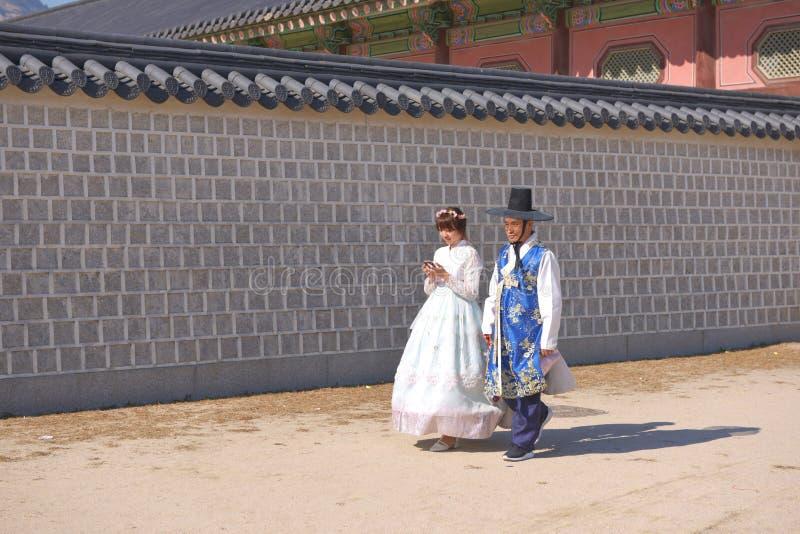 Seoul Sydkorea, November 2018: Koreanska mogna par klädde Hanbok i den traditionella klänningen som går i den Gyeongbokgung slott royaltyfri foto