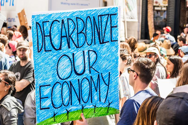 Sep 20, 2019 San Francisco / CA / USA - Decarbonize our economy placard raised at the Global Youth Climate Strike Rally and March royalty free stock image