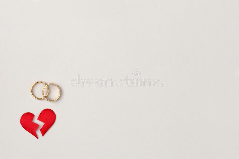 Separação vermelha do coração quebrado em duas partes com pares de alianças de casamento douradas, de vista superior, de conceito foto de stock