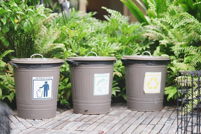 Separaci?n in?til 3 botes de basura clásicos en el jardín público con la basura general de la etiqueta, la basura mojada y recicl foto de archivo