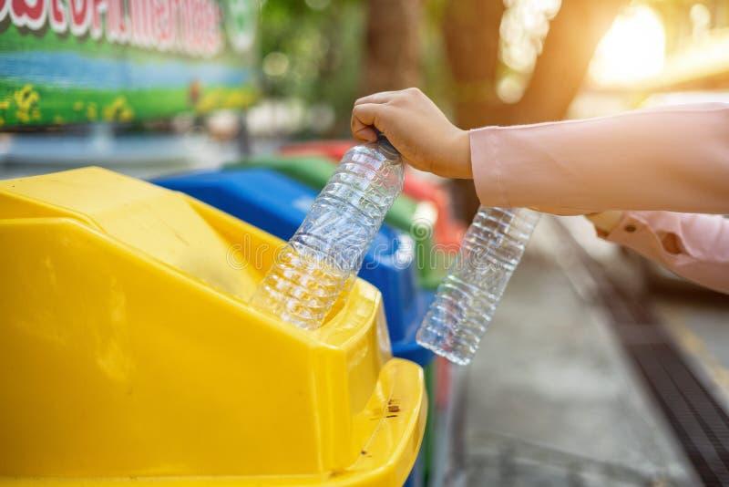 Separando le bottiglie di plastica residue nei recipienti di riciclaggio è di proteggere l'ambiente, non causante inquinamento, r immagini stock libere da diritti