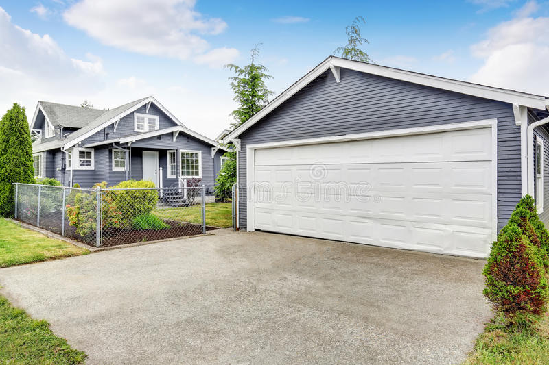 Separate garage with siding trim, concrete driveway and white door. Separate garage exterior with siding trim, concrete driveway and white door. Northwest, USA royalty free stock image