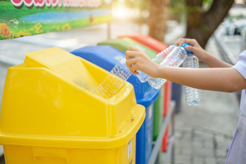 Separating waste plastic bottles into recycling bins is to protect the environment, causing no pollution, reduce global warming, stock photography