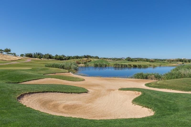Separatore di sabbia sul campo da golf con un lago fotografie stock libere da diritti