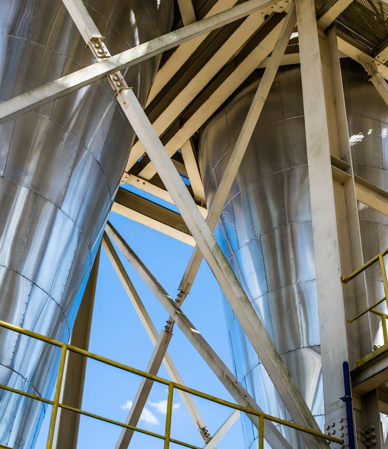 Separatori industriali d'acciaio brillanti sul fondo del cielo blu fotografia stock