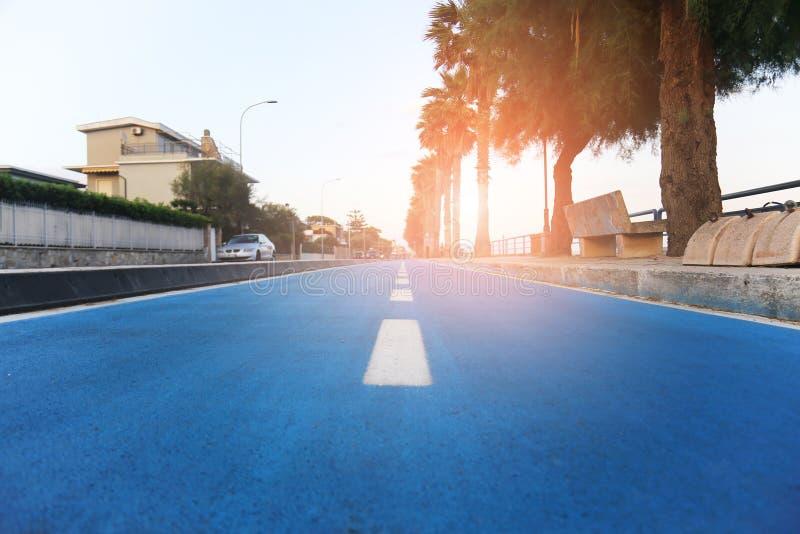 Separe a pista azul da bicicleta perto da praia no recurso do oceano Trajeto do ciclismo para o esporte e o estilo de vida saudáv imagens de stock