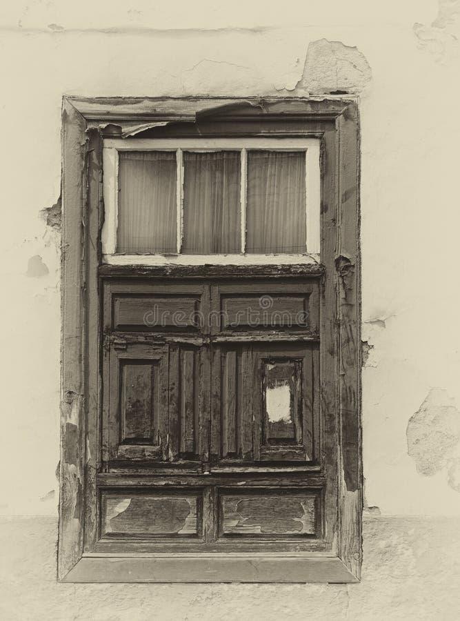 Sepia beeld van een oud Spaans shuttered venster in een traditioneel huis met langzaam verdwenen pleistermuren in sterk zonlicht stock foto's