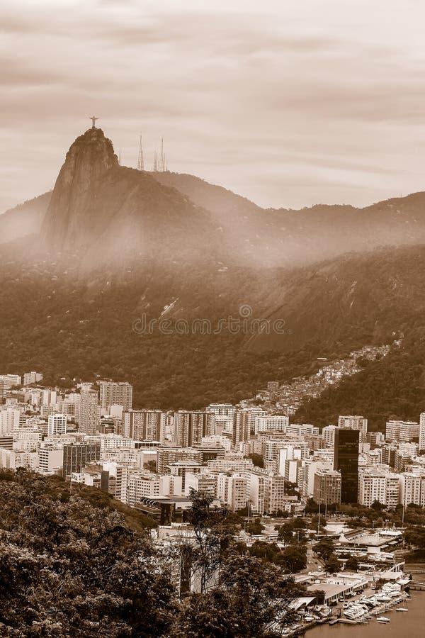 Sepia belebte Sicht auf die Stadt Rio de Janeiro mit Favelas in den Hügeln mit gemütlicher Statue auf dem Berg stockfotografie