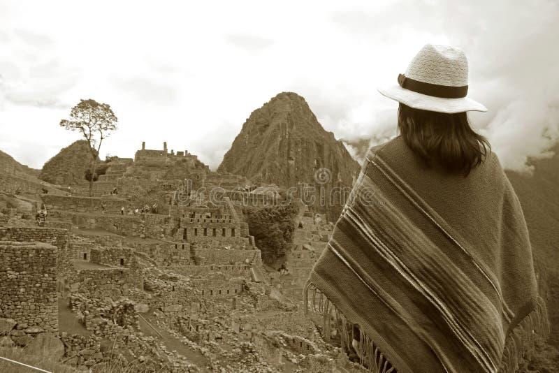 Sepia-Bild der Frau in Poncho Looking bei erstaunlichen Inca Ruins von Machu Picchu, Cusco-Region, Peru lizenzfreies stockbild