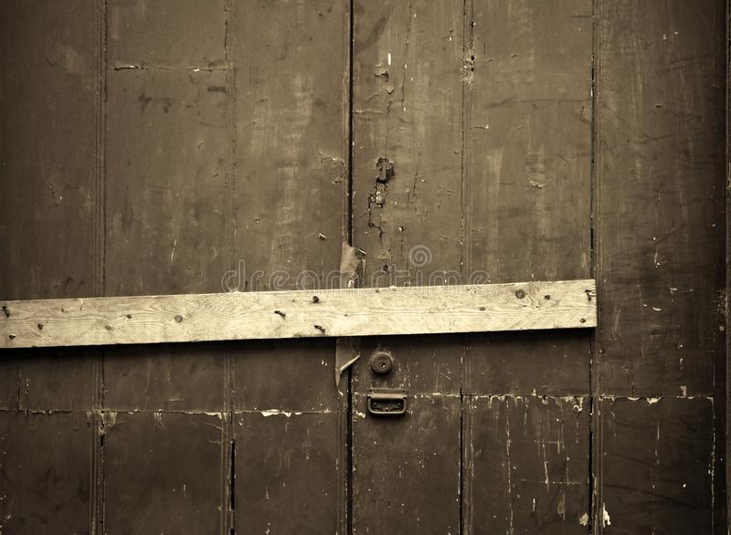 Sepia close up of an old cracked peeling wooden plank door barred shut with a piece of timber and rusty nails with a lock and. Handle stock photo