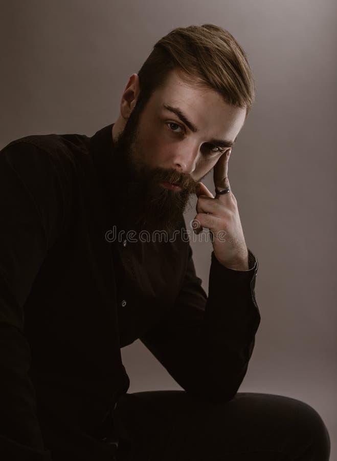 Sepia het fotoportret van een peinzende mens met een baard kleedde zich in het zwarte overhemd op de witte achtergrond stock afbeelding