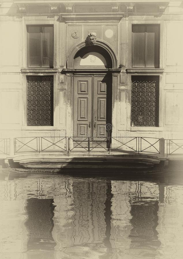 Sepia image of an old building along a canal in venice with shutters and doorway reflected in the water in bright sunlight and s. A sepia image of an old stock photo