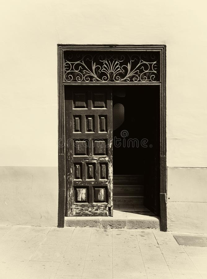 Sepia image of an old wooden door with panels in a traditional spanish house half open revealing stairs inside decorative ironwo royalty free stock image