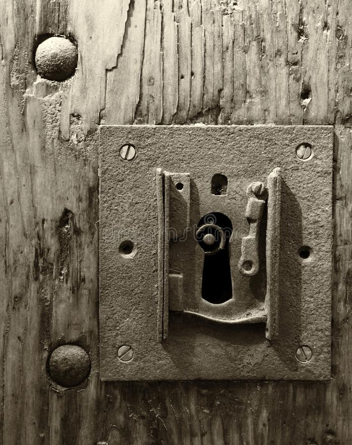 Sepia monochrome large square rusty iron lock with keyhole in an old wooden door and metal rivets. A sepia monochrome image of a large square rusty iron lock stock image