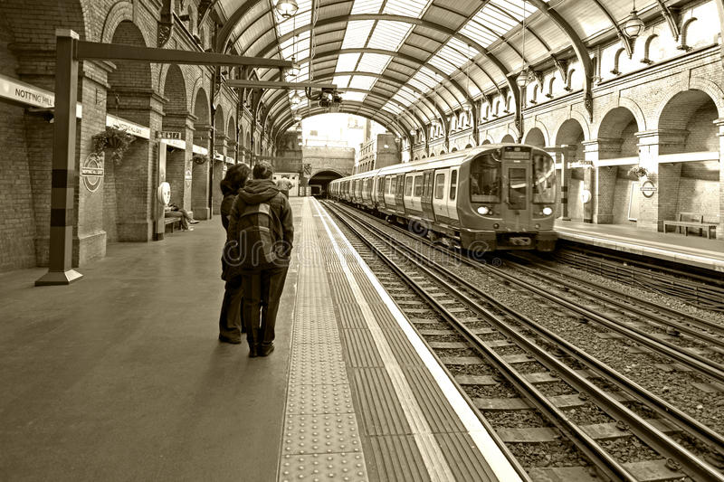 Sepia Photograph of train at Notting Hill Gate Station LOndon England. Passengers waiting for a train. Railway Station with Victorian architectural features royalty free stock photos