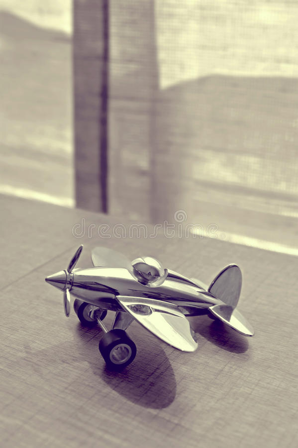 Sepia Photography of Stainless Steel Biplane on Brown Wooden Table Near Window during Daytime stock photography