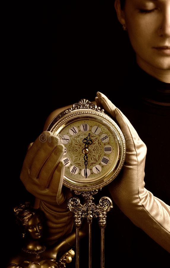 Sepia picture of a beutiful girl with a clock (focus on clock) stock photography