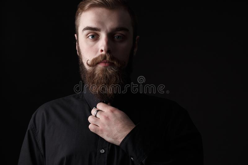 Sepia portrait of a stylish man with a beard and stylish hairdo dressed in the black shirt on the black background royalty free stock photo