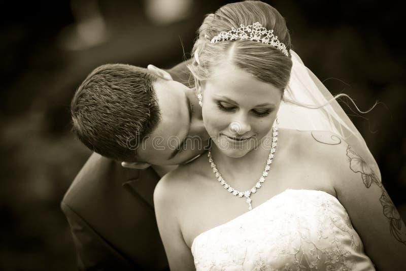 Sepia som kysser tatueringbruden på deras halshudbröllop arkivfoton