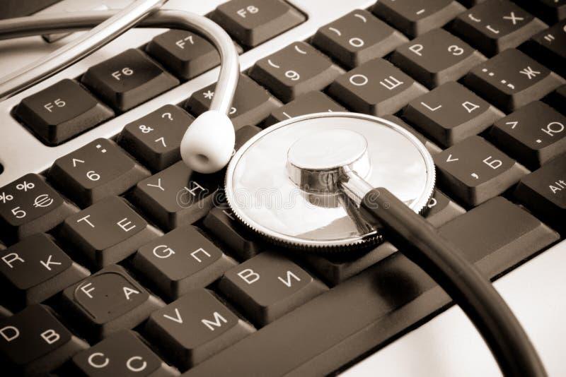 Sepia stethoscope at keyboard royalty free stock photo